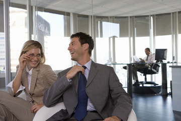 Businessman and woman laughing in armchairs in office, man at desk in background