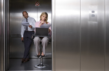 Businessman and woman looking at paperwork in lift, woman on stool, laptop on lap