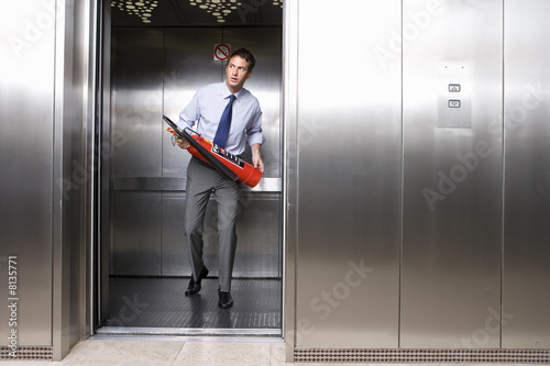 Young businessman holding fire extinguisher in lift