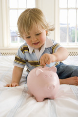 Baby boy (9-12 months) on bed putting coin in piggy bank, smiling, close-up