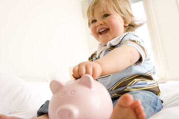 Baby boy (9-12 months) putting coin in piggy bank, smiling, low angle view