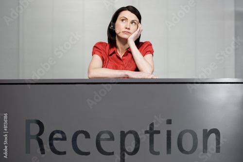 Office receptionist in a red blouse, looking bored