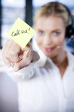 Businesswoman in a call centre with a sticky note saying Call Me