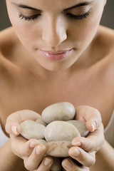 Young woman holding stones for heated stone therapy