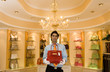 Male shop assistant, in white gloves, standing in front of shelf display in glamorous boutique, holding red designer handbag, front view, portrait
