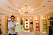 Male shop assistant, in white gloves, standing in front of shelf display in glamorous boutique, holding green designer handbag, front view, portrait
