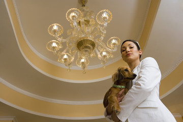 Young glamorous woman standing below chandelier, carrying dog, smiling, portrait, low angle view