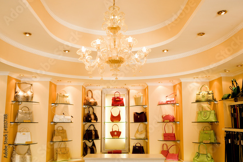 Selection of designer handbags on shelf display in glamorous boutique