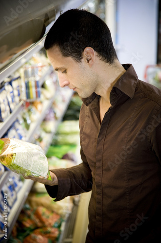 Man reading the label on food packaging in a supermarket