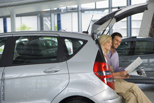 Couple looking at new silver hatchback in car showroom, sitting in open boot, man holding brochure, smiling, side view