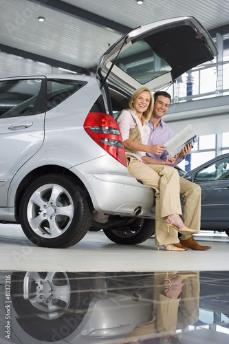 Couple looking at new silver hatchback in car showroom, sitting in open boot, man holding brochure, smiling, side view, portrait (surface level)