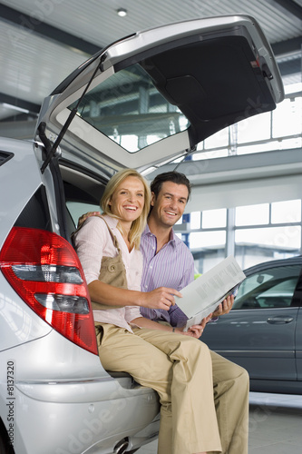 Couple looking at new silver hatchback in car showroom, sitting in open boot, man holding brochure, smiling, side view, portrait