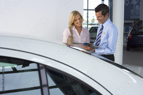 Car salesman standing with female customer in car showroom, man showing woman brochure, smiling, side view