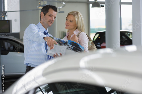Car salesman pointing out new car to female customer in showroom, holding brochure, smiling