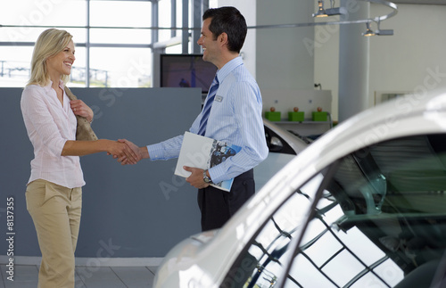 Car salesman shaking hands with female customer in showroom, man holding brochure, smiling, profile