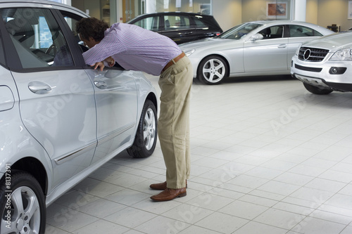 Man looking at new silver saloon car in showroom, leaning through open driver's seat window, side view