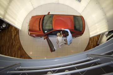 Couple looking at new red hatchback in car showroom, overhead view