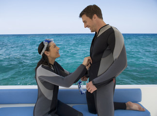 A couple on a boat preparing to go scuba diving