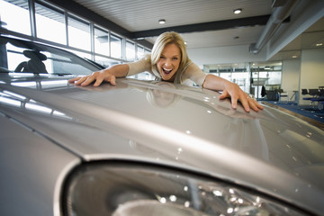 Excited woman embracing bonnet of new silver car in large showroom, smiling, portrait (surface level)