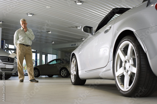 Senior man standing beside new silver convertible car in large showroom, smiling, portrait (surface level)