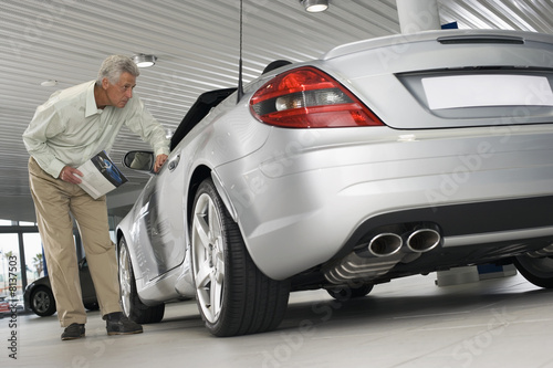 Senior man looking at new silver convertible car in large showroom, peering through window, holding brochure (surface level, tilt)