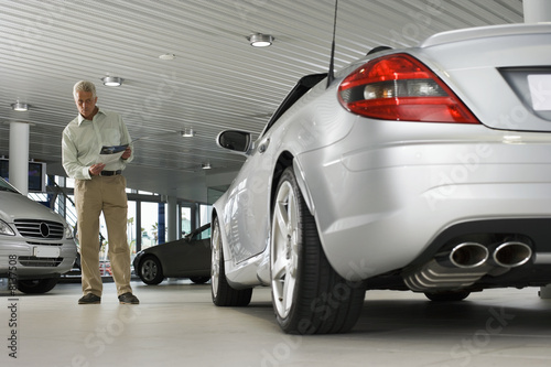 Senior man looking at new silver convertible car in large showroom, holding brochure (surface level)