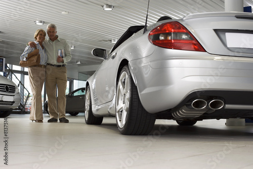 Senior couple looking at new silver convertible car in large showroom, man holding brochure, smiling (surface level)