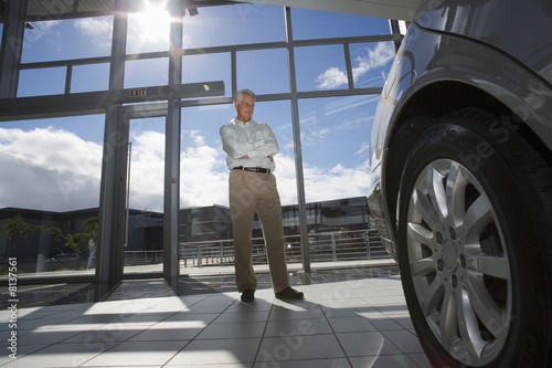 Senior man standing in car showroom, looking at new car (surface level, tilt, lens flare)