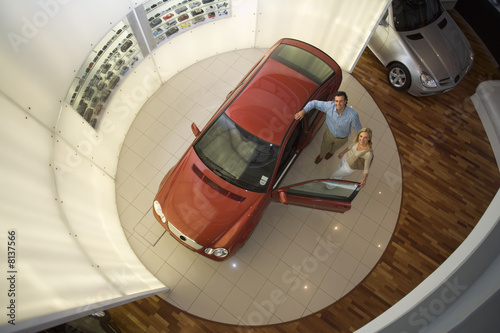 Couple looking at new red hatchback in car showroom, smiling, portrait, overhead view