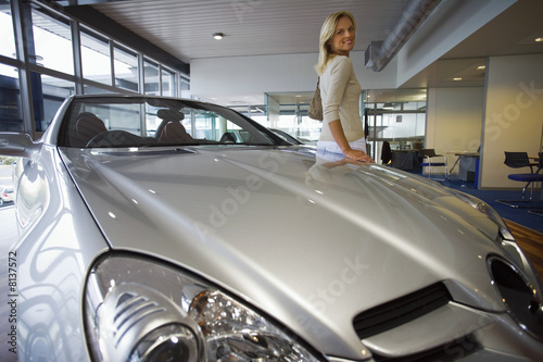 Woman leaning against new silver convertible car in large showroom, smiling, portrait