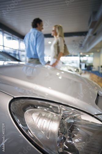 Couple holding hands in large showroom, focus on bonnet of new silver car in foreground, side view
