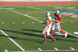 American football player chasing opposing receiver with ball during competitive game, side view