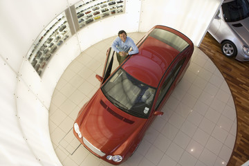 Man leaning against new red hatchback in large car showroom, smiling, portrait, overhead view