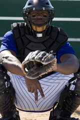 Baseball catcher crouching on pitch, making secret signal with fingers, front view, portrait