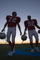 Two American football players leaving pitch at sunset, side by side, front view (surface level, backlit)
