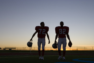 Two American football players leaving pitch at sunset, side by side, front view (backlit)