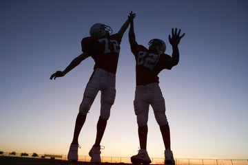 Two American football players celebrating on pitch at sunset, jumping up, doing high-fives (backlit)