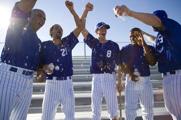 Baseball team, in blue uniform, punching air in victory post match, cheering (lens flare)