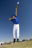 Baseball player, in blue uniform, jumping up to catch ball in protective glove during competitive game (surface level, tilt)