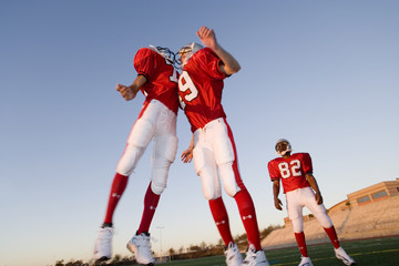 Two American football players, in red football strips, celebrating touchdown on pitch at sunset, jumping chest to chest, teammate looking on, low angle view (tilt)