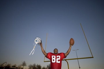 American football player, in red football strip, celebrating victory on pitch at sunset, arms up, holding ball and protective helmet in front of goal post, low angle view, portrait