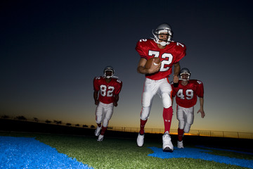 Three American football players, in red strips, running on pitch with ball at sunset (surface level)