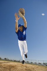 Baseball player, in blue uniform, diving to catch ball in protective glove during competitive game (surface level, tilt)