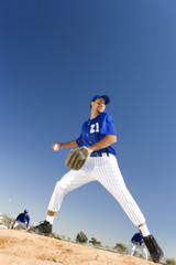 Baseball pitcher, in blue uniform, preparing to throw ball during competitive game (surface level, tilt)