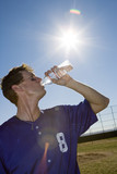 Sportsman drinking water from bottle on pitch, profile, low angle view (lens flare, tilt)