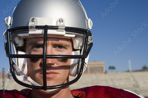 American football player wearing football strip and protective helmet, standing on pitch, close-up, front view, portrait