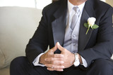Senior groom, in formalwear, sitting on chair at wedding, thumbs pressed together, mid-section