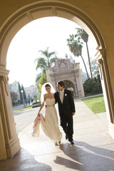 USA, California, San Diego, bride and groom walking arm in arm along pavement towards building arch, smiling, front view (tilt)
