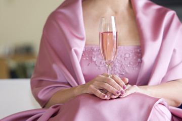 Senior woman, in pink dress, holding champagne flute at wedding, front view, close-up, mid-section