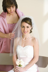 Bride sitting on bench at wedding, senior woman adjusting bride's veil, smiling, portrait